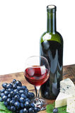 Glass of red wine with bottle and grape. Over white Royalty Free Stock Photography