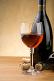 Glass of red wine and bottle with grape on wood Stock Photos