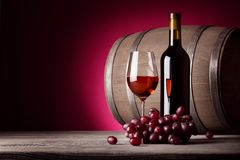 Glass of red wine with bottle and grapes Royalty Free Stock Images