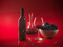 Glass red wine, bottle, grapes and pitcher. Glass of red wine, bottle, bowl woth grapes and decanter on red background Royalty Free Stock Photo