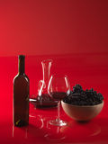 Glass red wine, bottle, grapes and pitcher. Glass of red wine, bottle, bowl woth grapes and decanter on red background Stock Photos