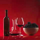 Glass red wine, bottle, grapes and pitcher. Glass of red wine, bottle, bowl woth grapes and decanter on red background Royalty Free Stock Photos