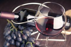 Glass of red wine with bottle and grapes Stock Photos