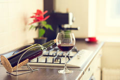 Glass of red wine with bottle on kitchen worktop Stock Photo