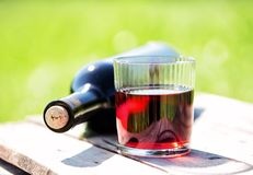 Glass of red wine and bottle lying on wooden table Stock Photography