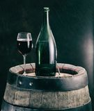 Glass of red wine and wine bottle on the oak wine keg. Royalty Free Stock Images