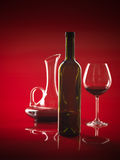 Glass of red wine, bottle and pitcher. Glass of red wine, bottle and decanter on red background Stock Photos