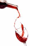 Glass of red wine and bottle. Red wine pouring in a glass isolated on white background Stock Photo