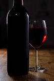 Glass of Red Wine and Bottle. A bottle of red wine and a glass resting on a wooden table Stock Photo