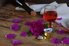 A glass of red wine, bottle, rose and ring on rustic wood table. Birthday, Mother`s day, Valentine`s Day, March 8, Wedding still. Life. Concept greeting card Stock Image