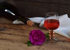 A glass of red wine, bottle and rose on rustic wood table. Valentines Day, Birthday, Mother`s day, March 8, Wedding still life. C. Oncept greeting card. Copy Royalty Free Stock Photo