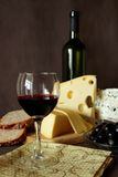 Glass of red wine, bottle and several varieties of cheese Stock Photography