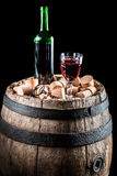 Glass of red wine and a bottle standing on a barrel Royalty Free Stock Photos