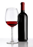 Glass with red wine bottle on white background Stock Photos