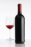 Glass with red wine bottle on white background stock images