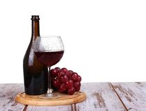 Glass with red wine, bottle of wine and grapes. Wine glass with red wine, bottle of wine and grapes on board isolated over white background royalty free stock images