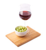 Glass of red wine and bowl of grapes Royalty Free Stock Image