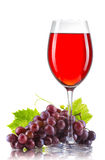 Glass of red wine and a bunch of ripe grapes isolated Stock Photography