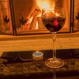 Glass of red wine and candle near cozy fireplace, in country house, winter vacation, horizontal. Tranquil scene before cozy fireplace, with glass of red wine and stock image