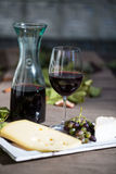 Glass of red wine, with carafe, cheese and grapes Stock Image