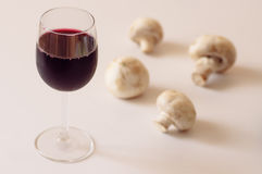 Glass of red wine and champignons. Pastel colour Stock Image
