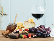 Glass of red wine, cheese board, grapes,fig, strawberries, honey and bread sticks  on rustic wooden table, blue Stock Photos