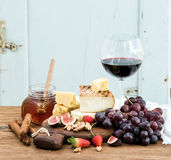 Glass of red wine, cheese board, grapes,fig, strawberries, honey and bread sticks  on rustic wooden table, blue Royalty Free Stock Image