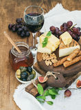 Glass of red wine, cheese board, grapes,fig, strawberries, honey and bread sticks  on rustic wooden table Stock Images
