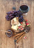 Glass of red wine, cheese board, grapes,fig, strawberries, honey and bread sticks  on rustic wooden table Royalty Free Stock Images