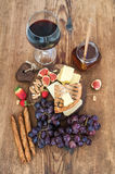 Glass of red wine, cheese board, grapes,fig, strawberries, honey and bread sticks  on rustic wooden table Royalty Free Stock Image