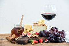 Glass of red wine, cheese board, grapes,fig, strawberries, honey and bread sticks  on rustic wooden table, white Stock Photo