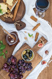 Glass of red wine, cheese board, grapes, walnuts, olives, honey and bread sticks on rustic wooden table Royalty Free Stock Photos