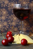 Glass of red wine, cheese and cherry royalty free stock image