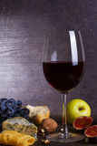 Glass of red wine, cheese, grape, walnuts, figs, plums and apple on wooden background. Royalty Free Stock Photography