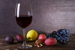 Glass of red wine, cheese, grape, walnuts, figs, plums and apple on wooden background. Stock Images
