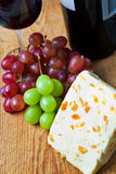 Glass of red wine with cheese and grapes Royalty Free Stock Images