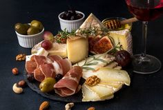 Glass of red wine and cheese plate with pieces moldy cheese, pro. Sciutto, pickled plums, olives, grapes, figs, honey, pear, nuts on black slate background royalty free stock photography