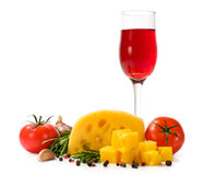 Glass of red wine , cheese , tomatoes , garlic and spices Royalty Free Stock Images