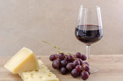 Glass of red wine with cheeses and grape. Royalty Free Stock Photo