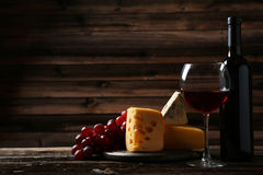 Glass of red wine, cheeses and grapes on the brown wooden background Stock Images