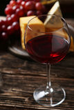 Glass of red wine, cheeses and grapes on brown wooden background Stock Image