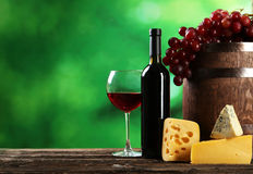 Glass of red wine, cheeses and grapes on the brown wooden background Stock Photo