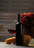 Glass of red wine, cheeses and grapes on a grey wooden background Royalty Free Stock Photos