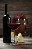 Glass of red wine, cheeses and grapes on the grey wooden background Royalty Free Stock Images