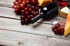 Glass of red wine, cheeses and grapes on the grey wooden background Royalty Free Stock Photo