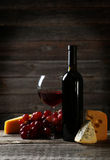 Glass of red wine, cheeses and grapes on the grey wooden background Royalty Free Stock Image