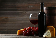 Glass of red wine, cheeses and grapes on a grey wooden background Stock Images