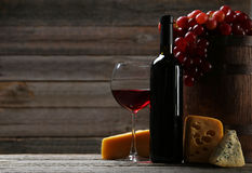 Glass of red wine, cheeses and grapes on a grey wooden background Royalty Free Stock Photo