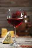 Glass of red wine and cheeses on the grey wooden background Stock Photography