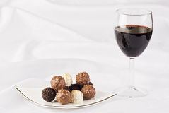 Glass of red wine and chocolate. Red wine and plate of chocolate on the table cloth Stock Images